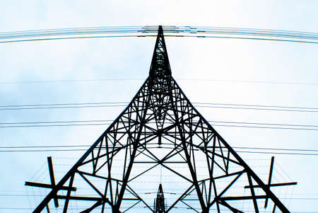 light transmission: looking upwards at a transmission tower with a light blue sky background