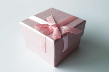 celebratory event: close up of a small square pink gift box with pink ribbon and pink bow on white background