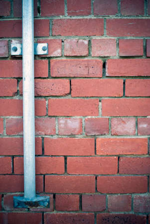 metal post: red brick wall background with metal post