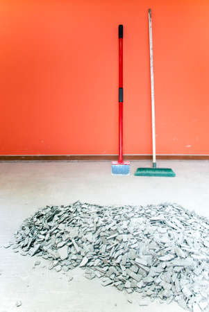 scraper: scraper and broom on concrete floor with pile of concrete tile adhesive Stock Photo