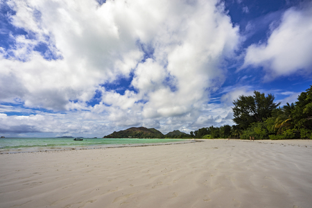 wide open paradise beach with white sand, palm trees and turquoise water on the seychelles. Simply paradise...