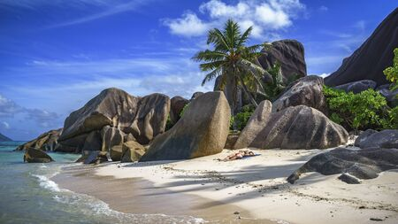 Girl is sunbathing between granite rocks and palm trees in the white sand at anse source dargent on la digue on the seychelles. Simply paradise...