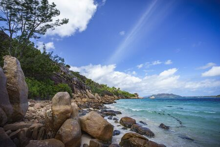 climas: A lot of granite rocks, turquoise water and a steep coast on seychelles beach.