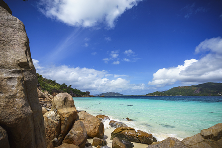 A lot of granite rocks, turquoise water and a steep coast on seychelles beach.
