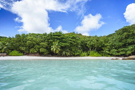 Standing in the turquoise water and looking to the picturesque dream beach with white sand, golden granite rocks, palm trees and a blue sky at anse lazio on praslin island on the seychelles. Simply paradise...