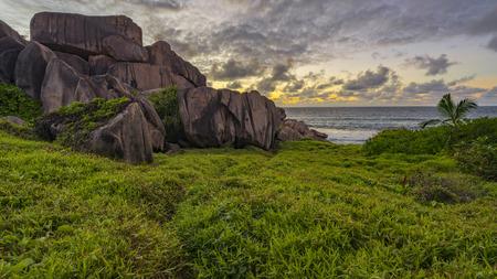 Weelderig groen gras en rode granietrotsen in de zonsopgang op La digue op de Seychellen.