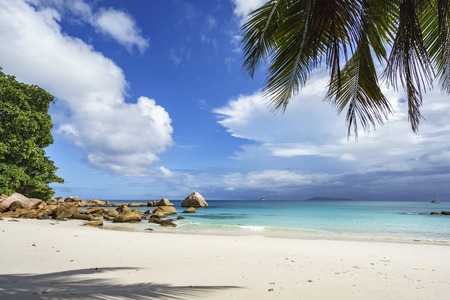 Picturesque dream beach with white sand, golden granite rocks, palm trees, turquoise water and a blue sky at anse lazio on praslin island on the seychelles. Simply paradise...