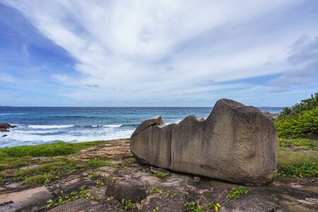 shrubbery: Impressive big granite rock in front of the indian ocean at the wild coast of anse songe, la digue, seychelles Stock Photo
