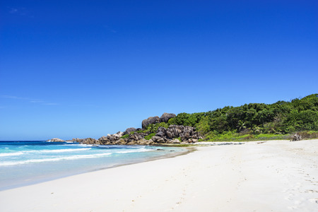 White sand, palm trees, granite rocks and turquoise water on a sunny day at  the big, wide paradise beach at grand anse, la digue, seychelles