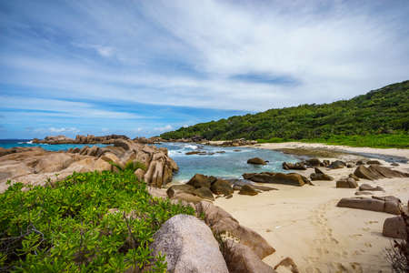 Hiking the rough and wild rocky coastline at anse songe, la digue, seychelles. lush green grass, palm trees, granite rocks and the indian ocean... Stock Photo