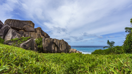 Hiking a footpath in the wilderness to mighty red granite rocks in lush green grass at anse songe, la digue, seychelles