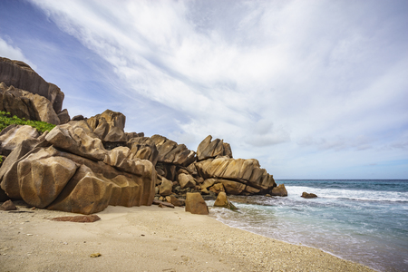 Mighty golden granite rocks in the sand of the beach at grand anse, la digue, seychelles