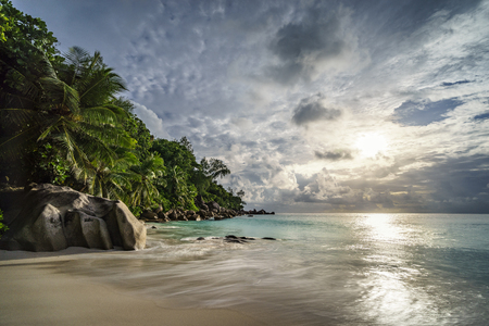 An approaching thunderstorm over the paradise. the sun shines bright under the black clouds and lightens up the palms, the granite rocks and the turquoise water of this beautiful dream beach at anse georgette on the seychelles