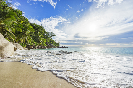 sunny day on paradise beach with big granite rocks, turquoise water, white sand and palm trees at anse georgette,praslin seychelles