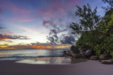 Spectacular romantic purple and orange colored sunset on paradise beach with granite rocks, palm trees sand and the ocean at anse georgette, praslin, seychelles