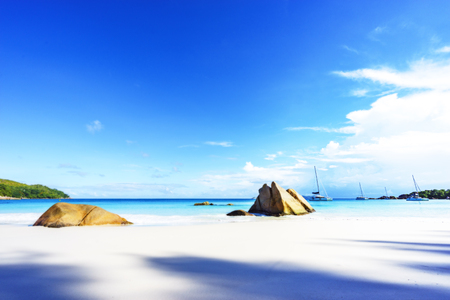Picturesque dream beach with white sand, golden granite rocks and catamarans in the turquoise water and a blue sky at anse lazio on praslin island on the seychelles. Simply paradise...