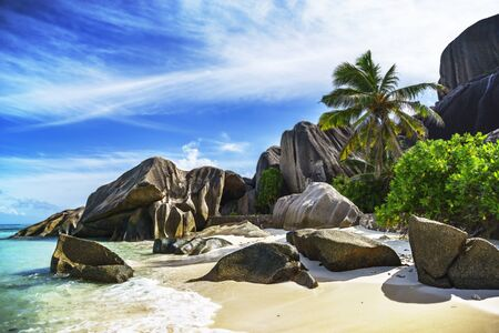 turquoise water, granite rocks and palm trees in the white sand of anse source dargent on the seychelles