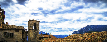 looking over the roofs on a little church in the mountains at lake garda under a dramatically cloudy sky.