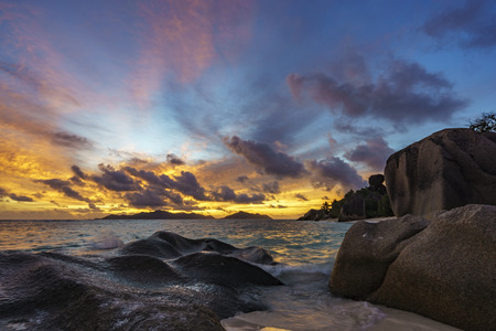 Romantic sunset over granite rocks and turquoise water at paradise beach, anse source dargent, la digue, Seychelles