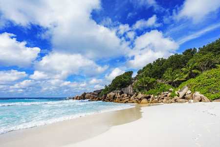 granite rocks, white sand, turquoise water, blue sky and palms on paradise beach on the seychelles, petite anse, la digue Stock Photo