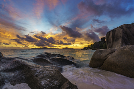 romantic sunset over granite rocks and turquoise water at paradise beach,anse source dargent,la digue,seychelles Stock Photo