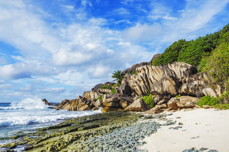 Granite rocks, white sand and palms on paradise beach on the Seychelles, grand anse, la digue Stock Photo