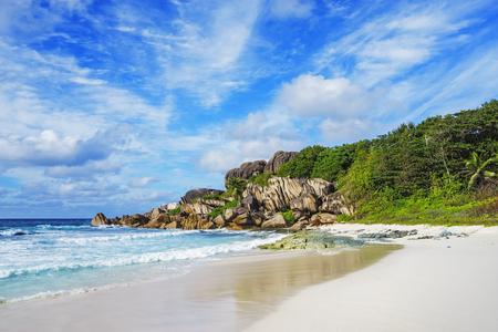 Granite rocks, white sand and palms on paradise beach on the Seychelles, grand anse, la digue Stock Photo