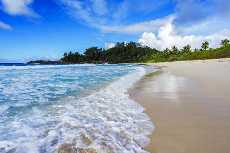 beautiful paradise beach with palms, white sand, turquoise water and granite rocks at the police bay on mahe, seychelles. Great resort Stock Photo