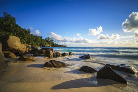 beautiful sunset at paradise tropical beach with granite rocks and their shadows, sand turquoise water, waves, anse intendance, mahé,seychelles  - long exposure Stock Photo