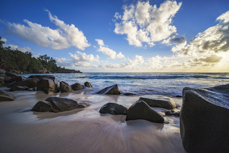beautiful sunset at paradise tropical beach with granite rocks, sand turquoise water, waves, anse intendance, mahé,seychelles  - long exposure Stock Photo