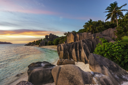 Beautiful sunset at amazing picturesque paradise beach. granite rocks,white sand,palm trees,turquoise water at tropical beach anse source dargent, la dique, seychelles