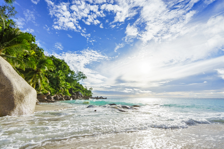 Amazing beautiful paradise tropical beach with granite rocks,palm trees and turquoise water in sunshine at anse georgette, praslin, seychelles Stock Photo
