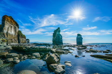 blue water, golden rocks and sand. on the beach, 3 sisters and elephant rock, new zealand