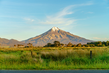 on the road, lush grass, farms and cows infront of cone volcano mount taranaki, new zealand 写真素材