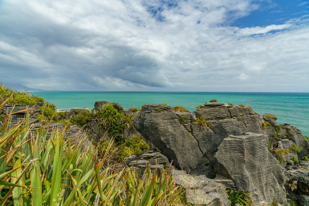 rock formation at the steep coast of the pacific oceanon a cloudy day. punakaiki pancake rocks, west coast, new zealand 写真素材