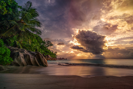 Sunbeams during sunset behind a big cloud at anse georgette on praslin on the seychelles 스톡 콘텐츠