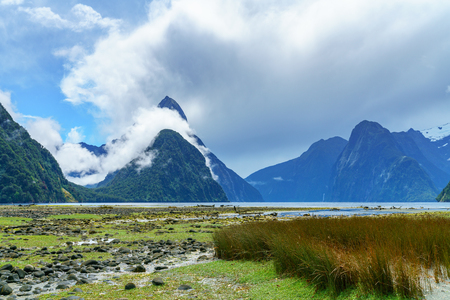 mountains in the clouds, famous milford sound, fiordland, new zealand Standard-Bild - 114581823