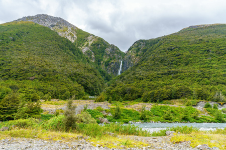 hiking in the mountains. devils punchbowl waterfall, arthurs pass, new zealand