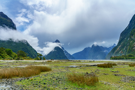 mountains in the clouds, famous milford sound, fiordland, new zealand Standard-Bild - 114654912