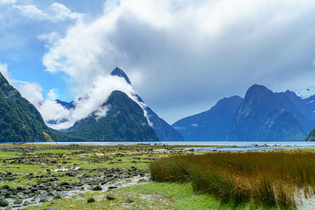 mountains in the clouds, famous milford sound, fiordland, new zealand Standard-Bild - 114655103