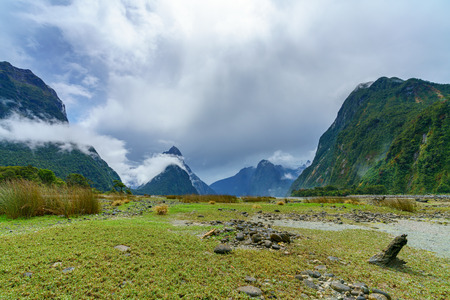 mountains in the clouds, famous milford sound, fiordland, new zealand Standard-Bild - 114655546