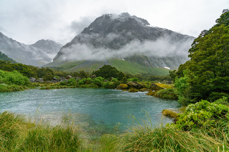 turquoise water of a river in the mountains in the rain, gertrude valley lookout, southland, new zealand Imagens