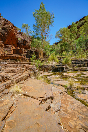 hiking over rocks in dales gorge, karijini national park, western australia