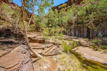 hiking over rocks in dales gorge, karijini national park, western australia Stock Photo
