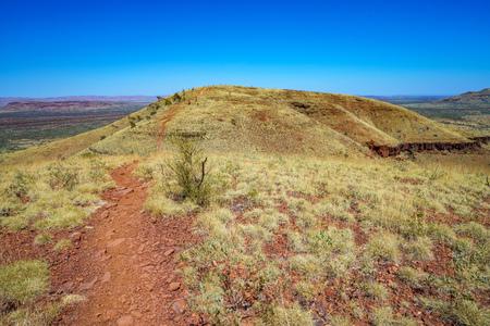 hiking on mount bruce in the desert of karijini national park, western australia