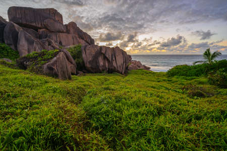 Granite rocks in lush green grass at anse songe on la digue on the seychelles