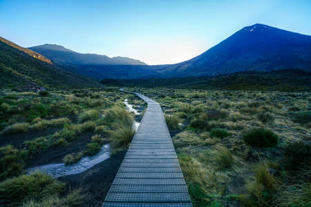 hiking the tongariro alpine crossing with cone volcano mount ngauruhoe at sunrise in new zealand