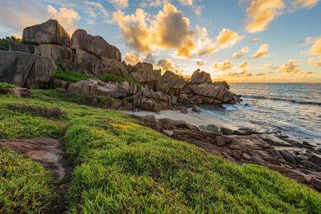 sunrise at tropical rocky coastline at anse songe on la digue on the seychelles 免版税图像