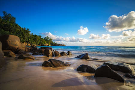 beautiful sunset at paradise tropical beach with granite rocks and their shadows, sand turquoise water at anse intendance, mahé, seychelles