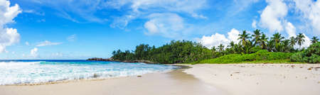 Beautiful and wild lonely tropical beach with rough granite rocks, white sand, palm trees in a jungle and turquoise water of the indian ocean at police bay on the seychelles Imagens